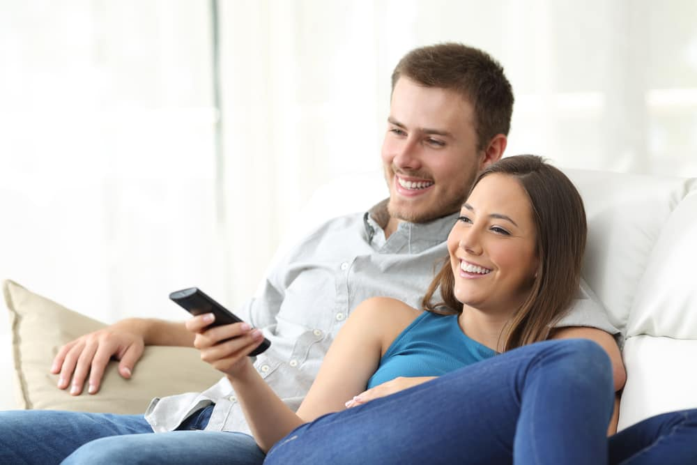 A couple sits on the sofa and watches a movie or show together