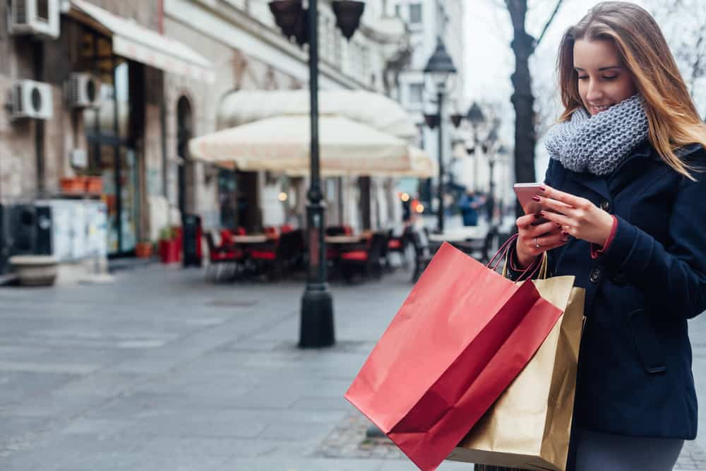 A woman looks at her mobile phone while she holds shopping bags