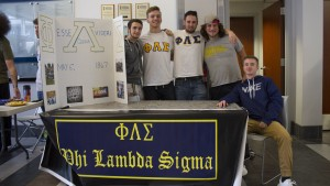 Members of Phi Lambda Sigma host a table in Mund