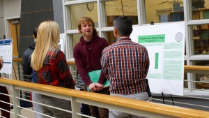 A psychology student presents research to faculty during a poster session