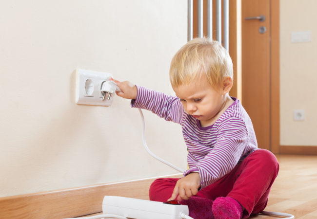 Baby playing with electrical outlet