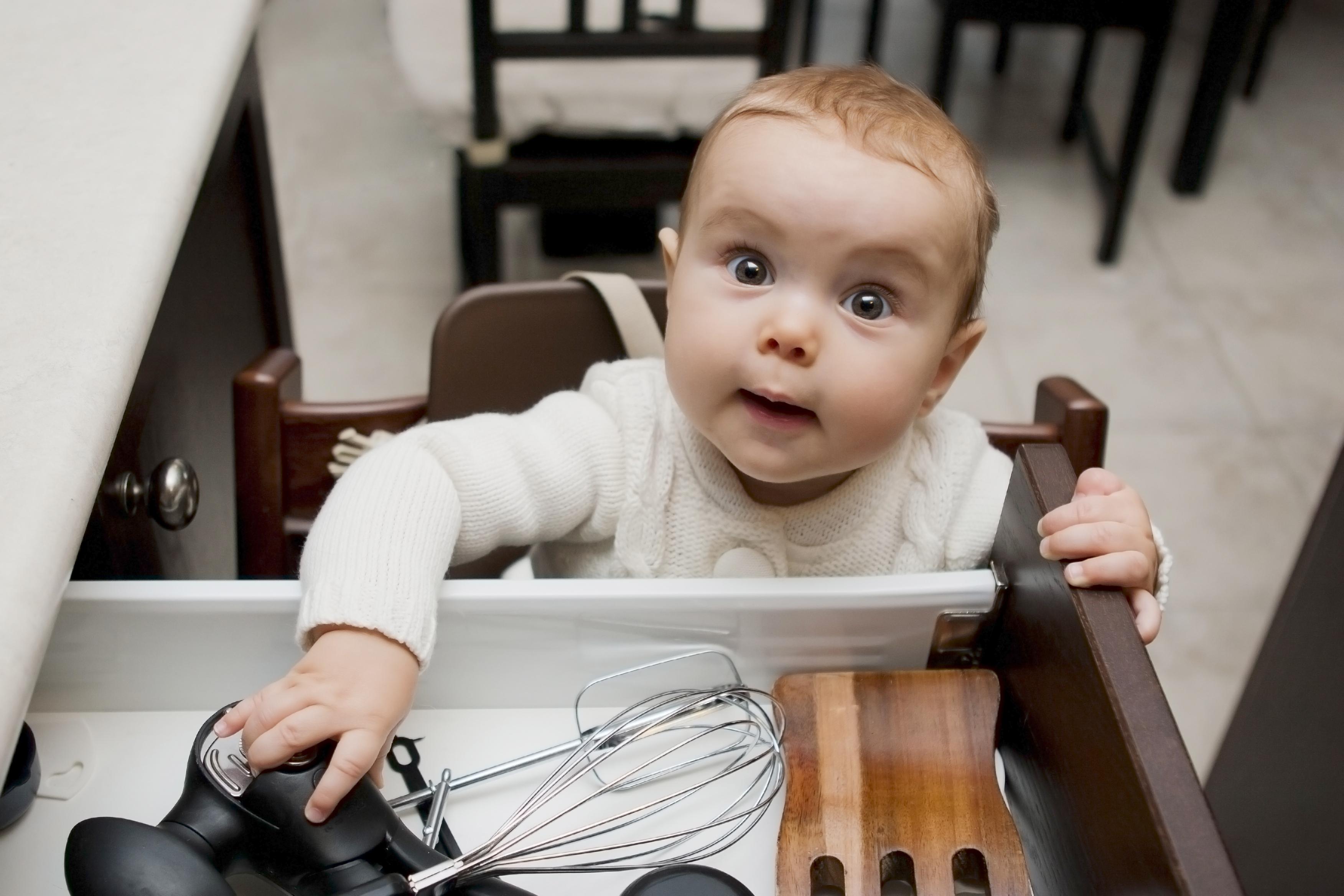 Baby reaching in kitchen drawer