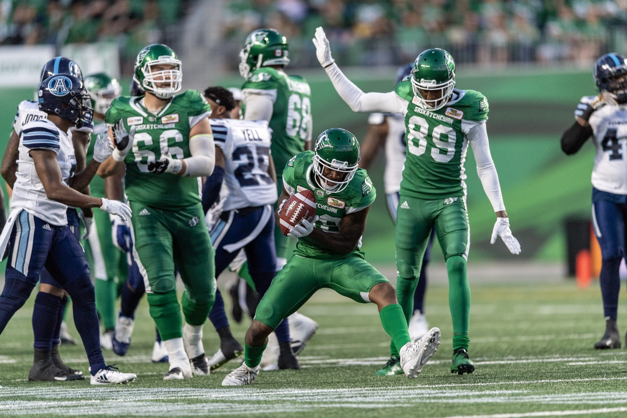 Saskatchewan Roughriders players celebrating during a CFL game