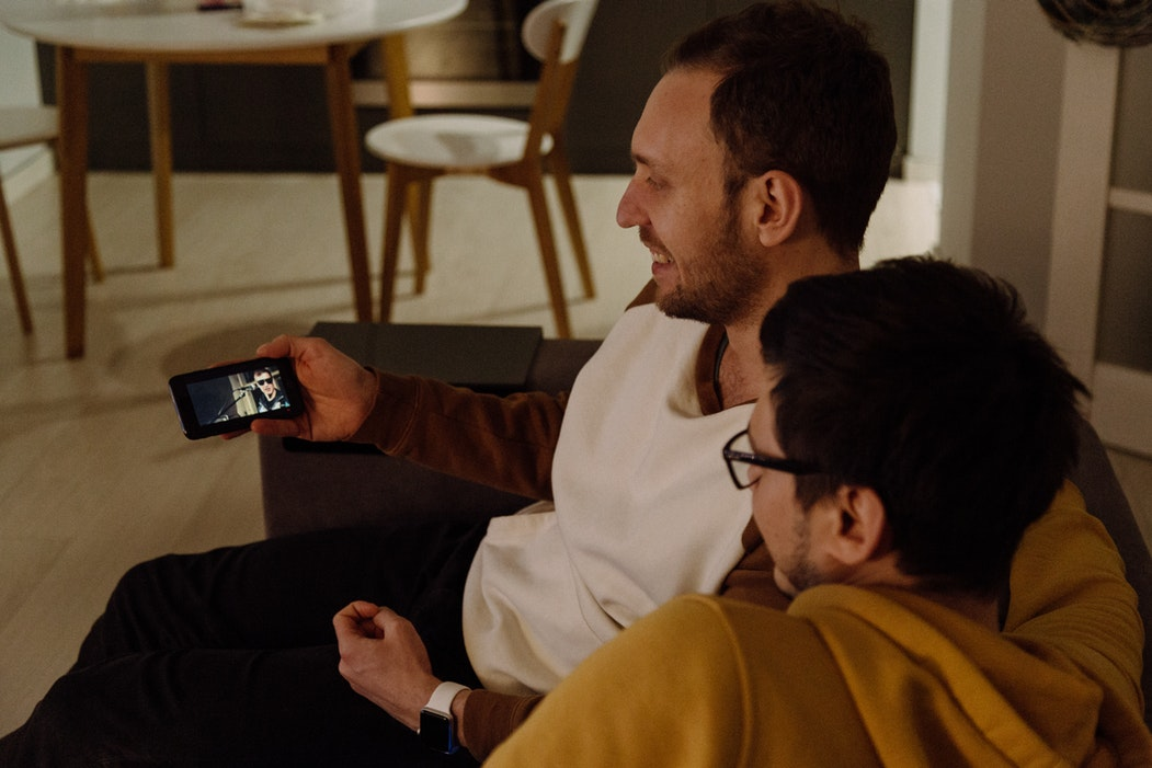 Two male friends watching a video on their smart phone