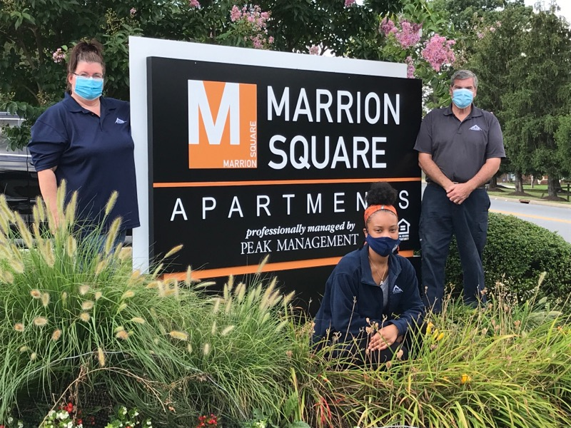 Marrion Square Team at entrance sign celebrating Apartment Teams Day