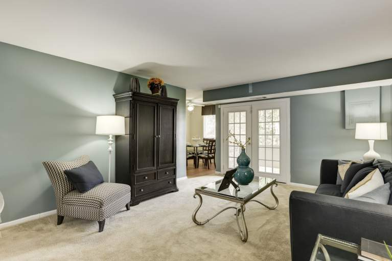 Living room with French doors to a private patio or balcony at Tuscany Woods Apartments
