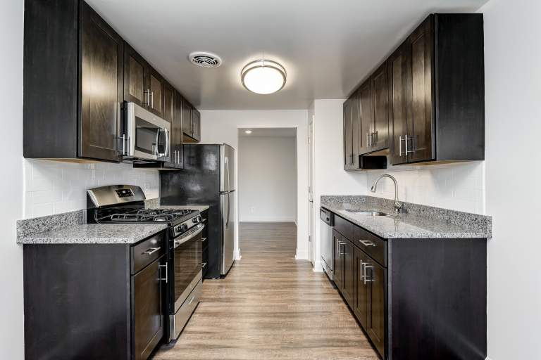 Renovated kitchen with granite countertops, stainless steel appliances, and upgraded kitchen package at Marrion Square Apartments.