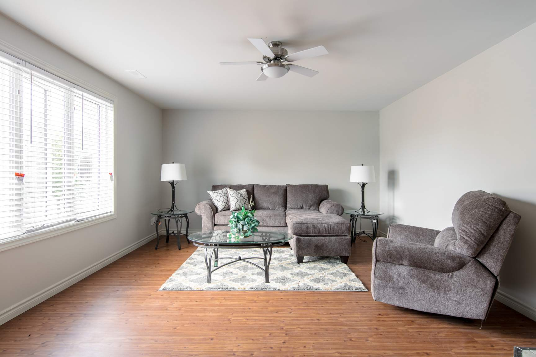 Large living room with new flooring and ceiling fan