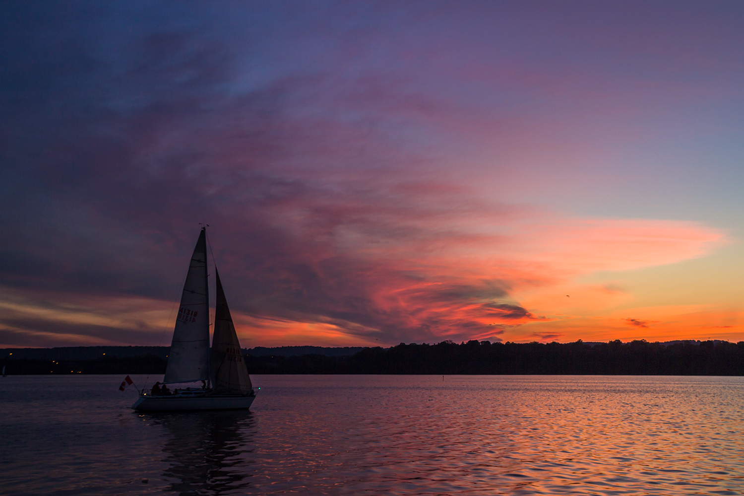 Photo of sail boat on water with sunset in background