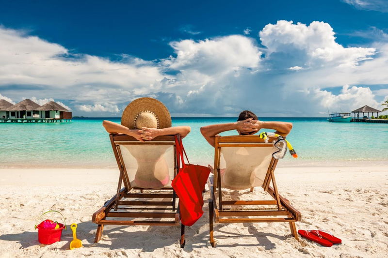 man and woman in beach chairs overlooking sea from sandy beach