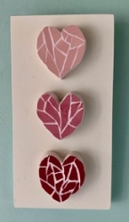 Mosaic three pink hearts on a white board