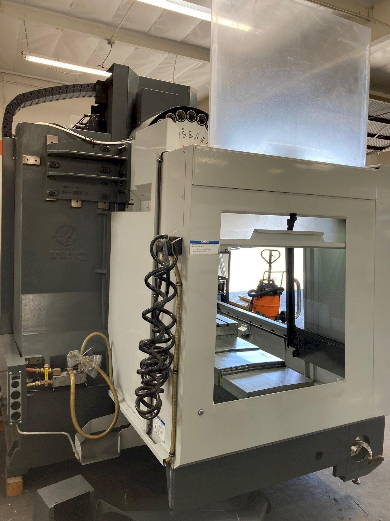 Haas VF-3 VMC 2012 with: Haas CNC Control, 24-Side Mount Tool Changer, 10,000 RPM Spindle, High Intensity Lighting, Mounted Tool Holder, Chip Auger, and Coolant Tank.