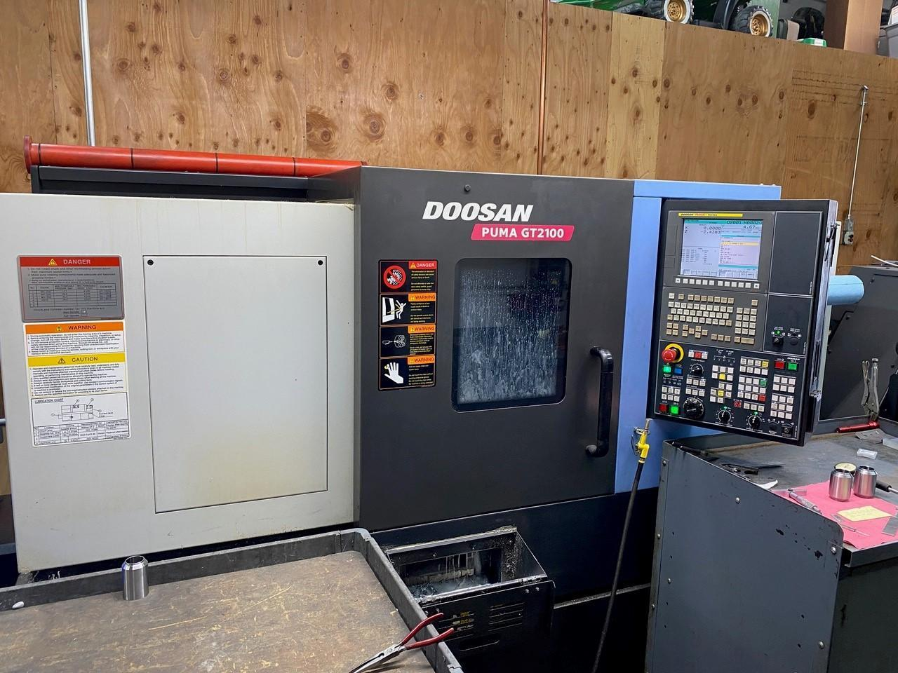 Doosan Puma GT-2100 HTC 2014, Fanuc i Series CNC Control, Tailstock, Tool Presetter, Parts Catcher, Barfeed Interface, and LNS Turbo HB Chip Conveyor.