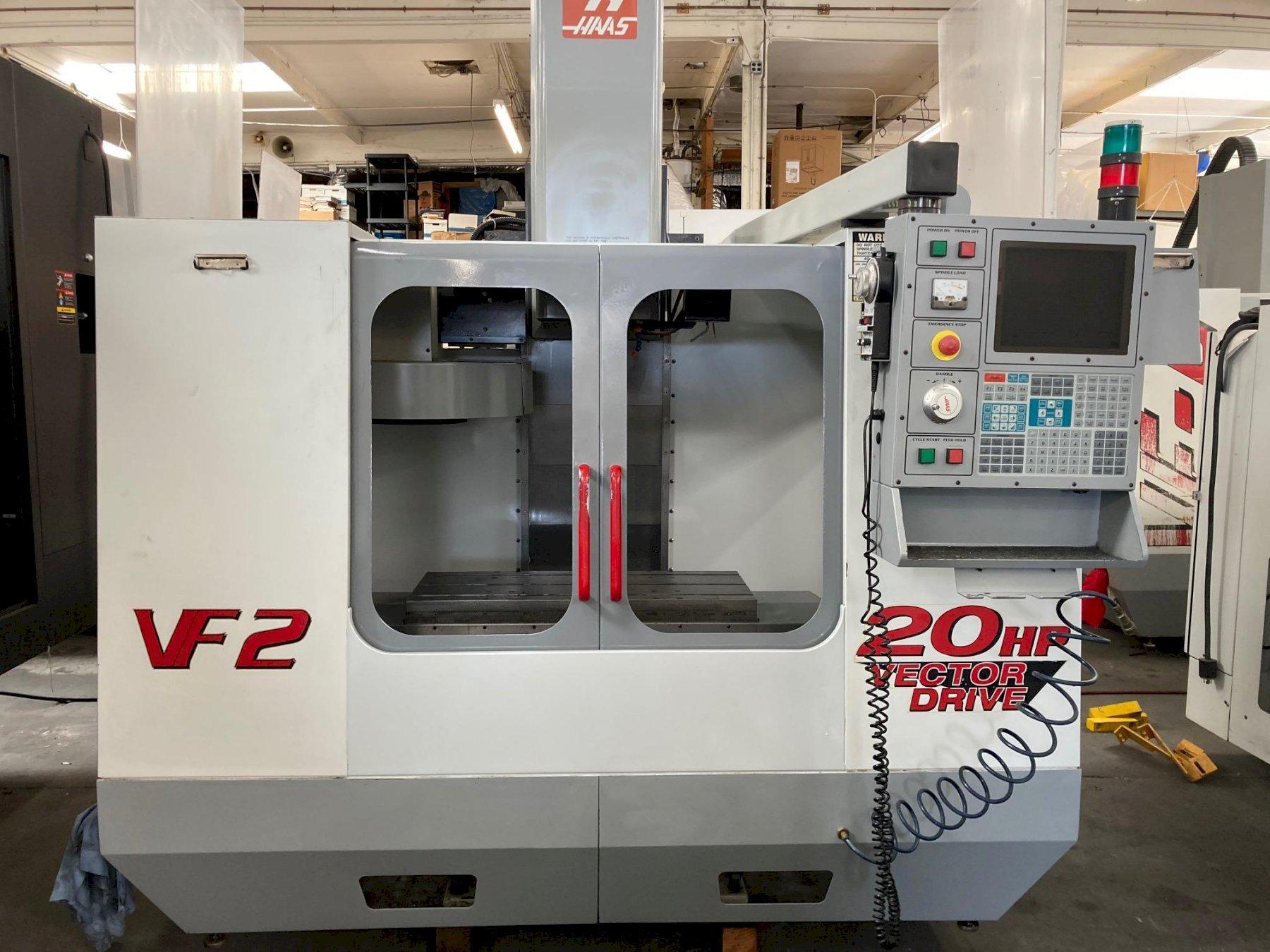 Haas VF-2 VMC 2000 with: Haas CNC Control, Programmable Coolant Nozzle, 20-HP Vector Drive, RJH, Chip Auger, and Coolant Tank.