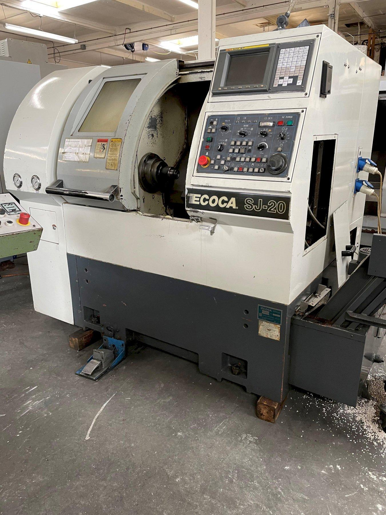 Ecoca SJ-20 CNC Lathe 2000 With: Fanuc 18-T CNC Control, 8-Station Turret, 5C Collet Nose, Tailstock, and Chip Conveyor.