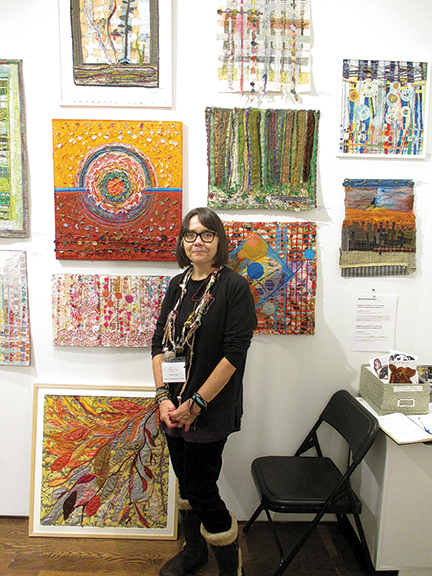 Alyson Vega, a textile artist whose work is shown through Fountain House Gallery, New York City, in front of some of her work.