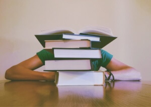 stack of books in front of a student - how hard is the lsat?