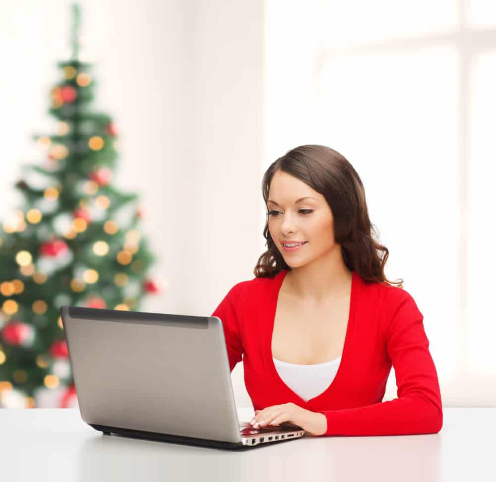 Woman completes Praxis holiday prep on her laptop with Christmas tree behind her