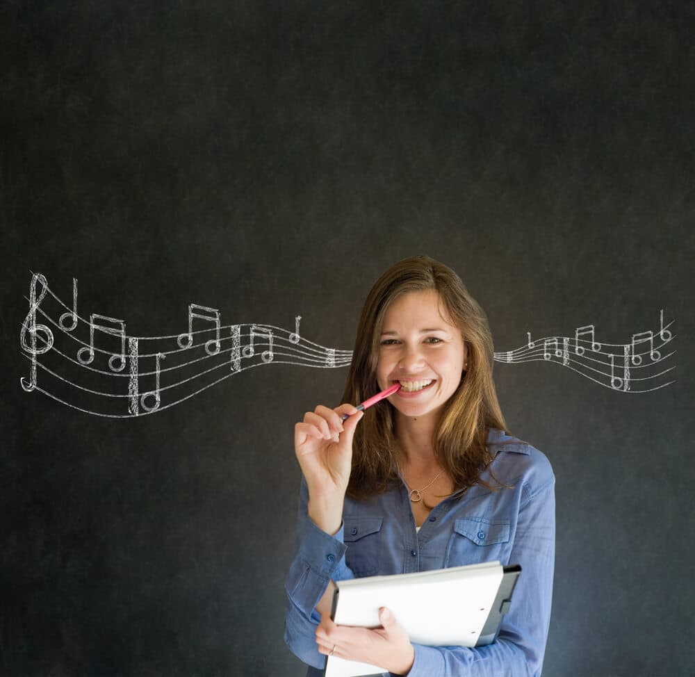 Teacher listens to fun teaching songs in front of a chalkboard