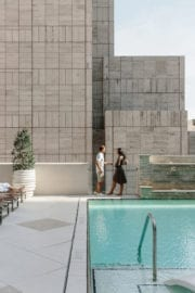 A couple standing beside the rooftop pool
