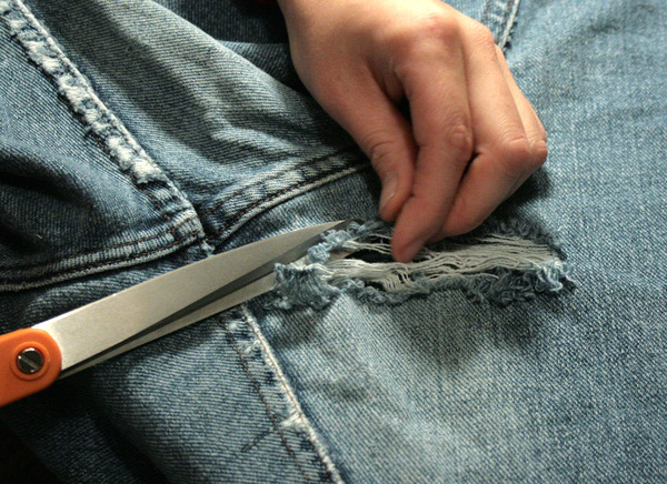 cutting off frayed edges from a hole in a pair of jeans