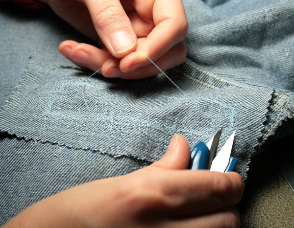 snipping the extra thread from a jean repair