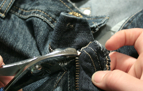 pliers pulling off the bottom stop of a pair of jeans