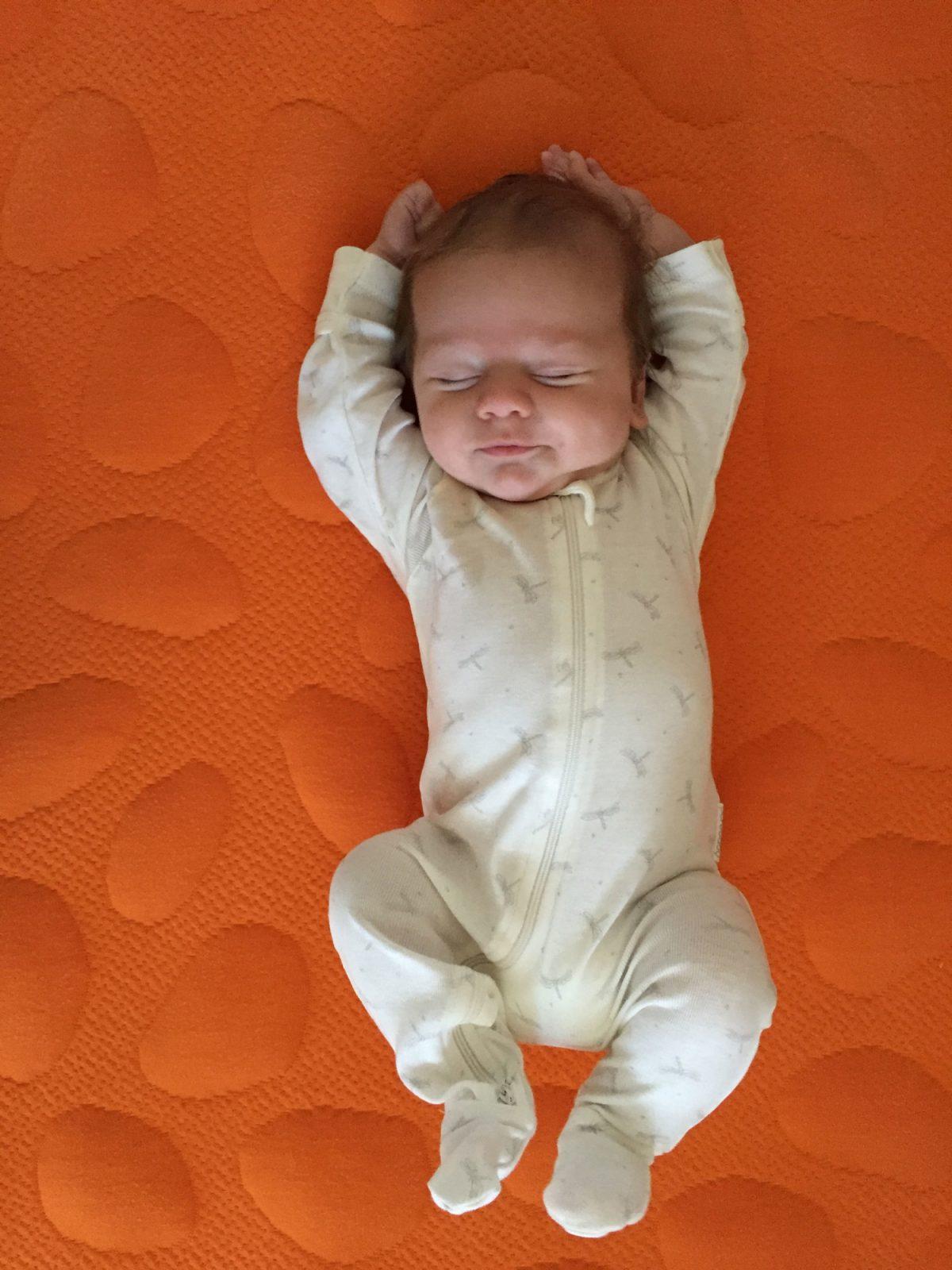 infant on orange nook crib mattress