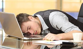 man-sleeping-on-desk web