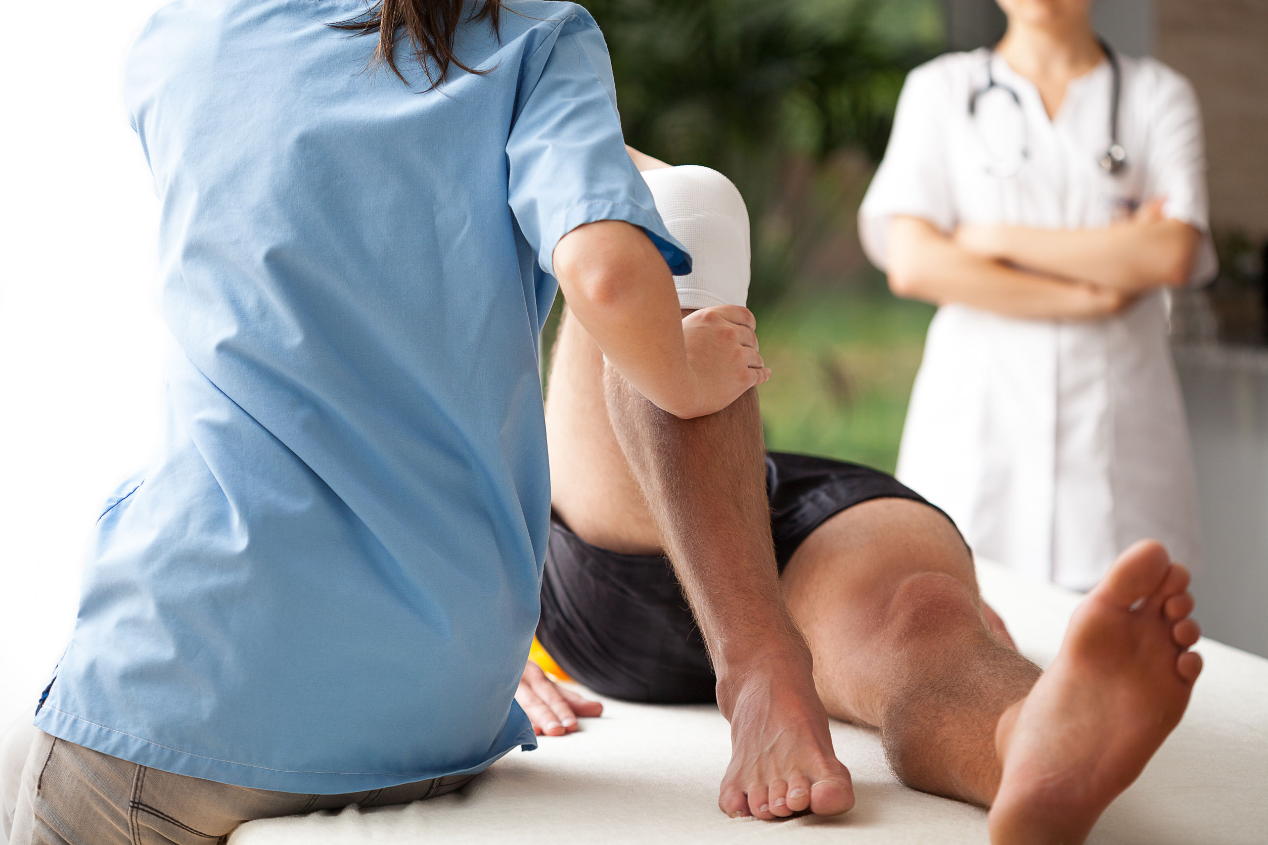 physical therapist helping male patient