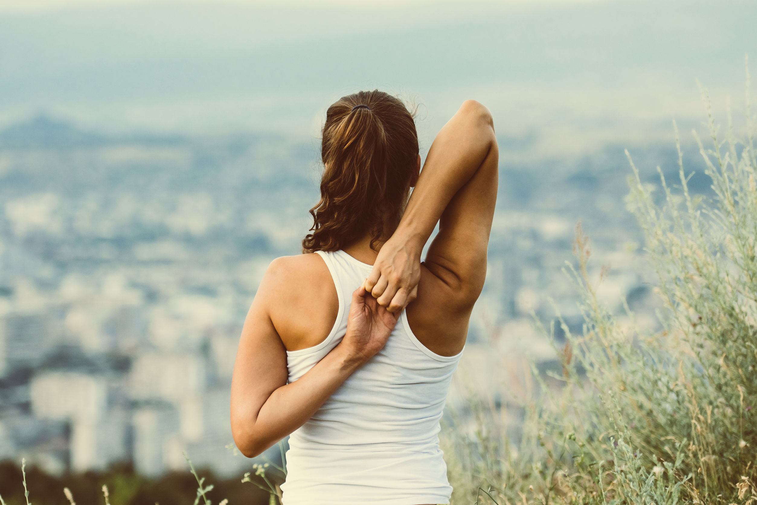 young woman stretching outside overlooking the city