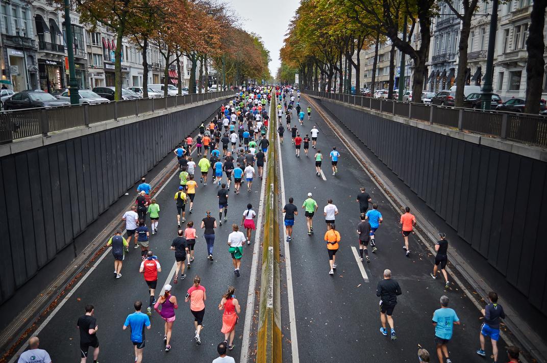 Runners running up a street hill.