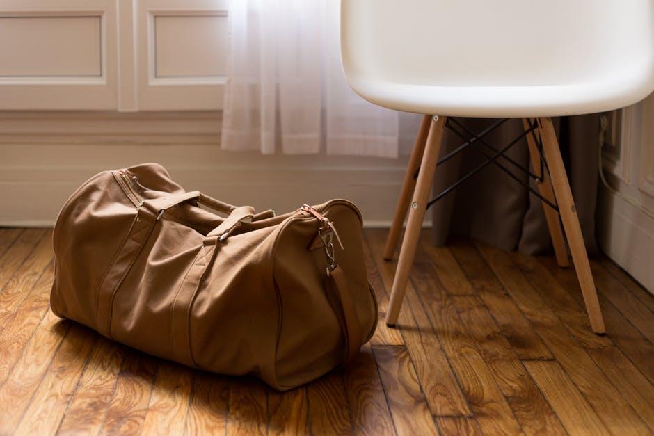 Brown duffel bag next to white chair
