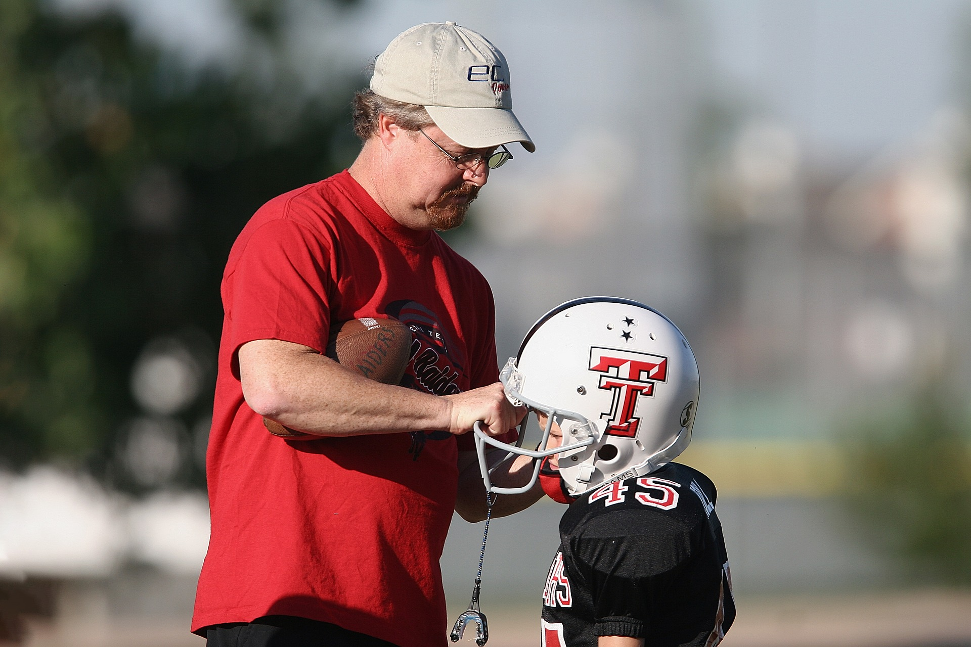Youth football coach adjusting player's helmet