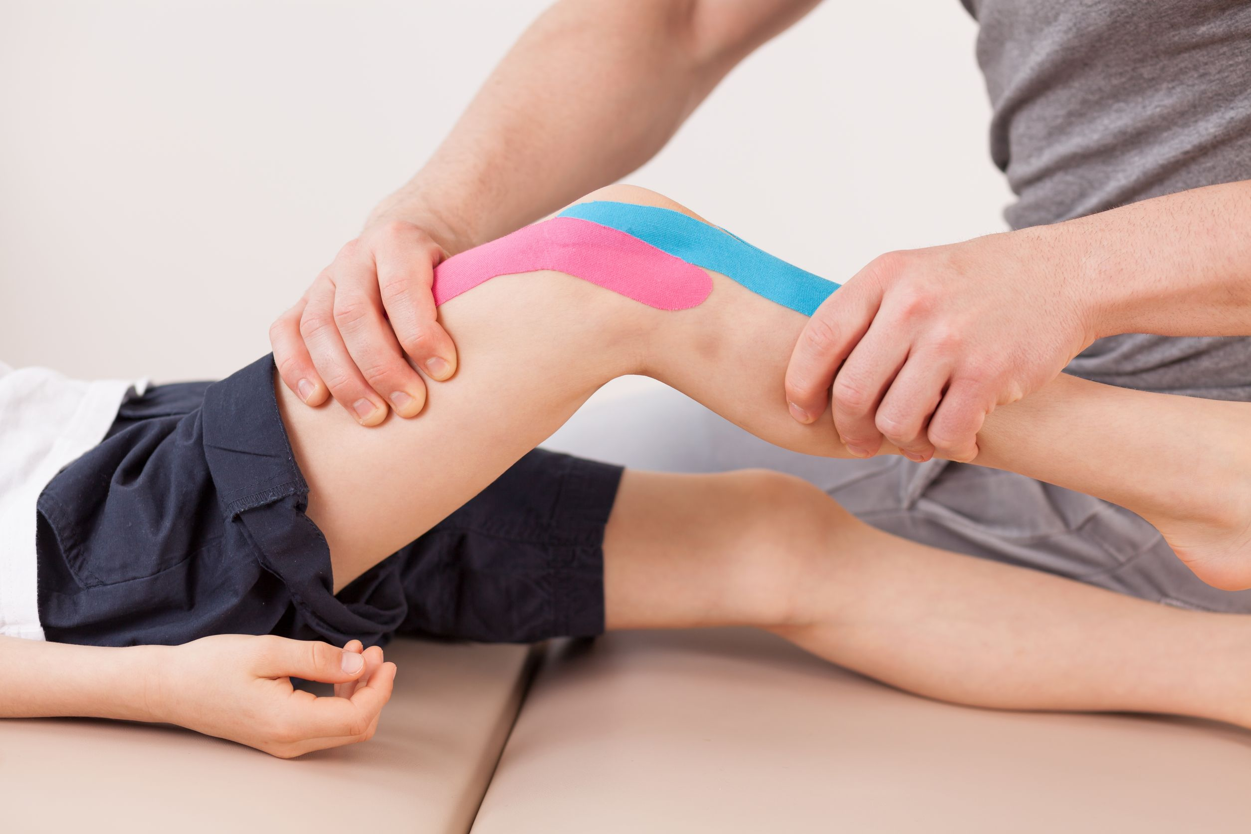 physical therapist working young boy's knee
