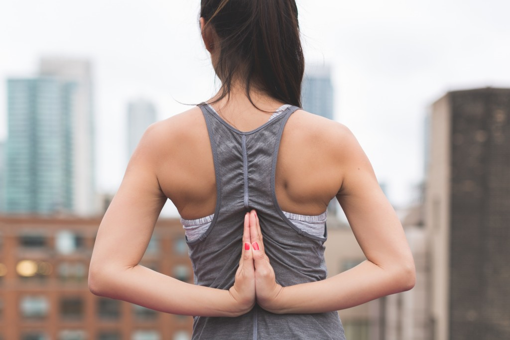 woman stretching arms behind her back