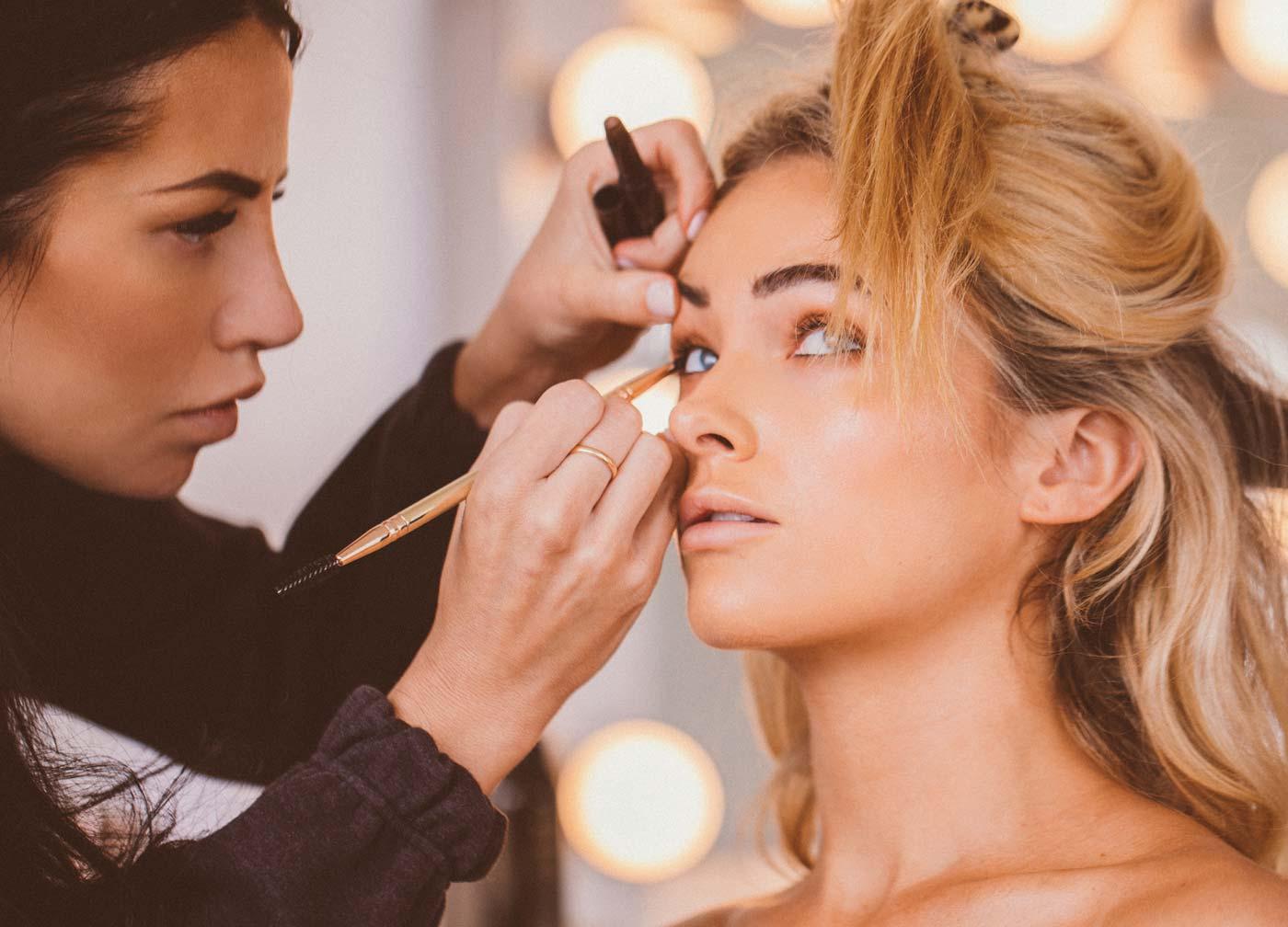 Cara applying Maskcara makeup on a model