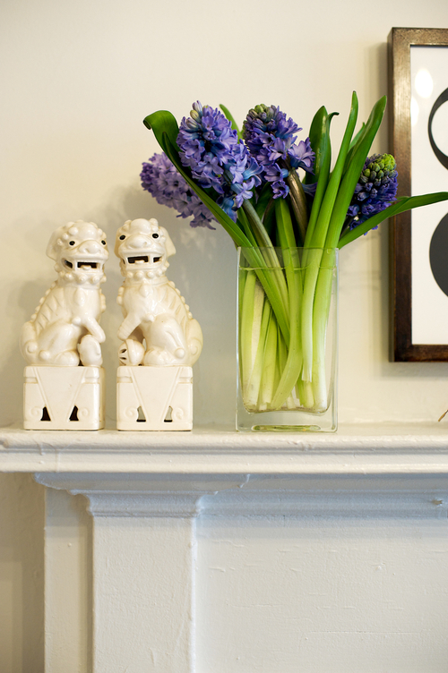 Simple fireplace mantel with foo dogs and flowers