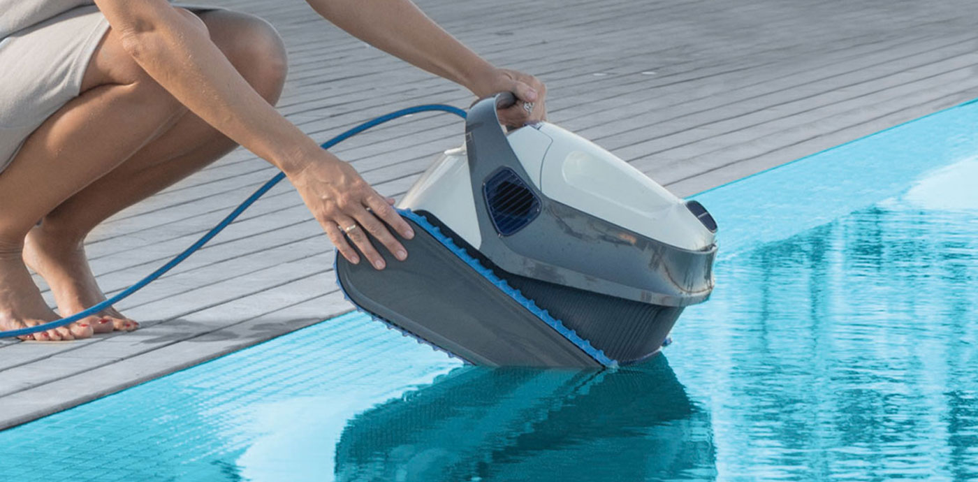 Woman Placing Dolphin Robotic Pool Cleaner in Pool