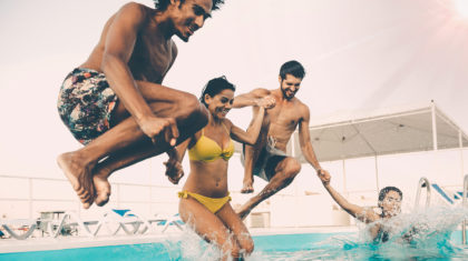 happy people jumping in pool