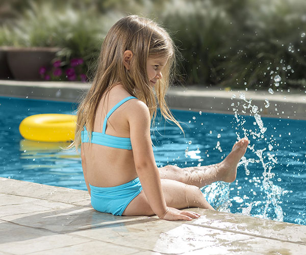 Child splashing at the edge of a clean swimming pool