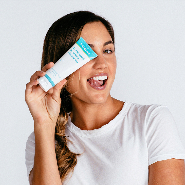 Woman using MDacne's Customized Soothing Moisturizer to prevent dry skin and acne