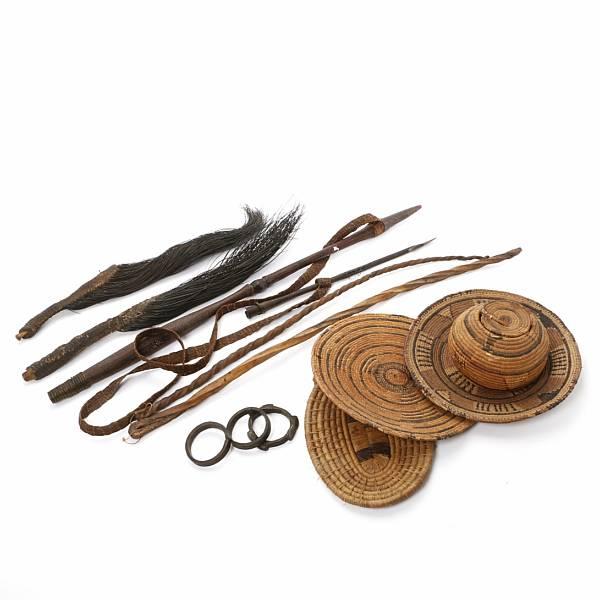 An African hippo harpoon, a basket, 3 trays, 2 flue swoops, 2 sjambok and 3 brass money braclets.