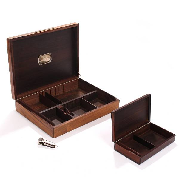 Danish design: Two Brazilian rosewood cigar boxes, one with appertaining Brazilian rosewood cigar cutter. H. 4. L. 18. W. 10 and H. 6. L. 29.5. W. 22 cm. (3)