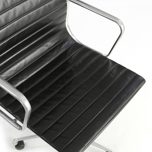 "Charles Eames, Ray Eames: ""Aluminium Group Side Chair"". Office chair with chromed aluminum frame. Seat and back upholstered with black leather."