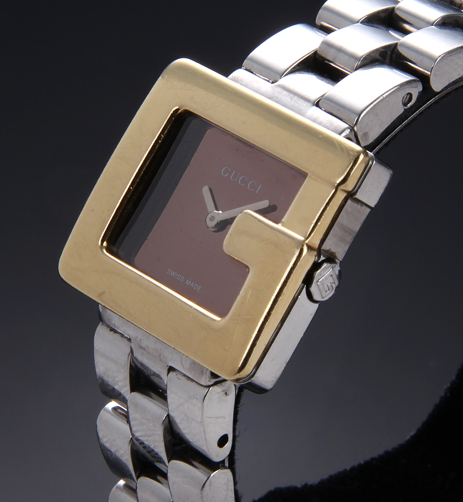 Gucci 'G'. Ladies watch in 18 kt. or steel, black plate, about 2000