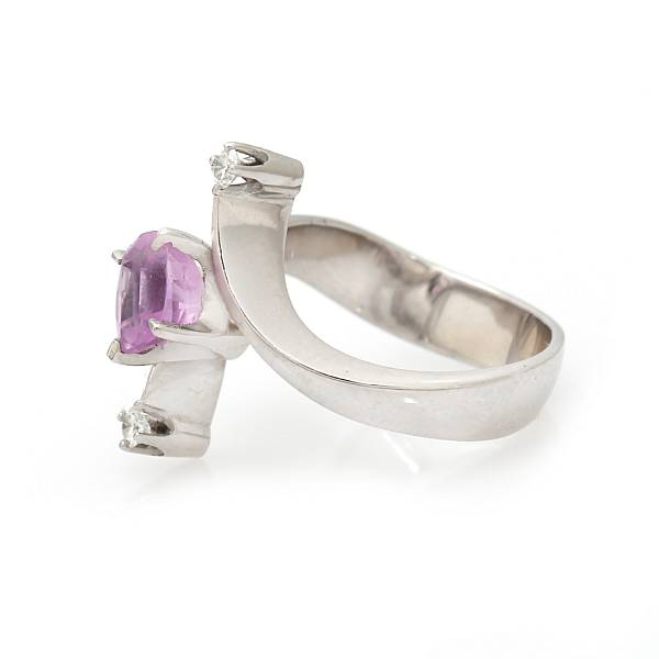 Georg Jensen & Wendel: A sapphire and diamond ring set with an oval-cut pink sapphire flanked by two brilliant-cut diamonds, mounted in 18k white gold. Size 57.