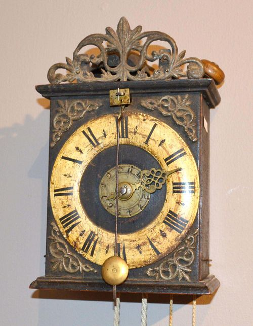 WALL CLOCK WITH ALARM AND FRONT PENDULUM,Baroque, Switzerland. Blackened wood with open-worked tin ornament. Fronton with wood chapter ring and alarm disc. Verge escapement. Alarm on bell. H 27 cm.