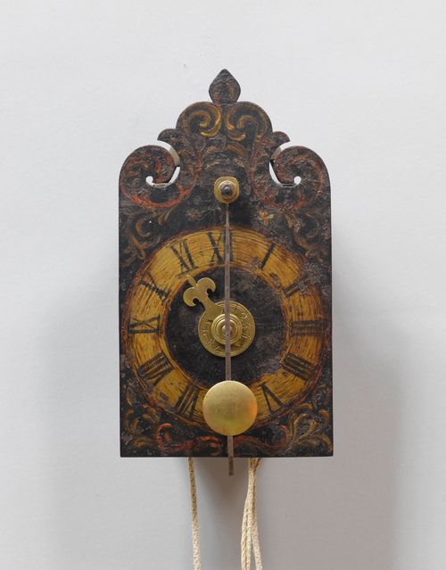 A SMALL IRON CLOCK WITH FRONT PENDULUM AND ALARM,