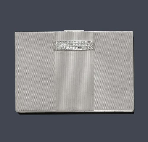 PLATINUM AND DIAMOND POWDER BOX, VAN CLEEF & ARPELS, ca. 1930. Platinum, 175g incl. mirror. Rectangular, engine-turned box, the centre decorated with 1 broad, ribbed band motif, the sprung cover with 1 appliqued barrette motif set throughout with 69 single-cut diamonds weighing ca. 1.00 ct. The pusher is additionally decorated with 5 diamonds. Inside compartment with cover for the powder, 2 corners of the mirror have minimal chip. Signed van Cleef & Arpels No. 42.762, VCA mark and platinum mark. Ca. 8.5 x 5.5 x 1 cm.